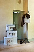 Bag, hat and jacket on coat stand next to open interior door and stacked white vintage wooden boxes