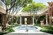 Fountain, plants and arcades in elegant, Mediterranean courtyard