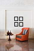 Orange armchair on stone floor below pictures on wall