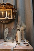 Artistic, vintage-style headdresses below gilt-framed mirror sconce with lit candles