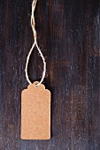 Brown paper tag with cord on dark wooden surface