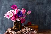 Strauß mit Frühlingsblumen vor einer schwarzen Wand