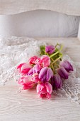 Pink and purple tulips on lace doily on white chair