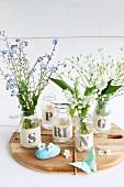 Frühlingsblumen in Gläsern mit Stoffbanderole und Buchstaben