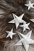 Aus weißem Papier gefaltete Sterne auf einem Fell
