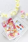 Papierblüten in einer Schachtel und zur Kette aufgefädelt