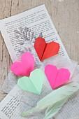 Origami-Herzen und Federn auf Buchseiten und Seidenpapier