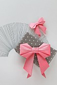 Pink origami bow on gift wrapped in polka-dot paper