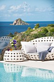 White outdoor furniture next to pool with view of sea and rocky island