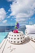 Flowers on white side table in front of sea and clouds in blue sky