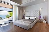 Schlafzimmer mit Polsterbett und Panoramablick aufs Meer