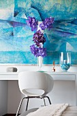 Vertical flower arrangement in front of blue picture on white console table