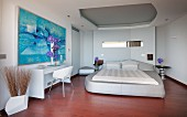 Upholstered bed and abstract art in futuristic bedroom