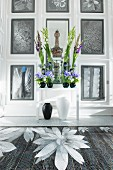 Luxuriant flower arrangement in front of floral artworks on panelled walls