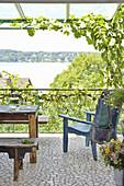 Balkon mit rustikalen Holzmöbeln und Seeblick