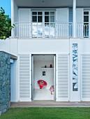 Haus mit Terrassenbauweise, Blick durch offene Fensterläden