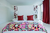 Red accents and floral patterns in white bedroom