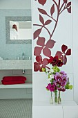 Flowers on bedside table and view into bathroom with mosaic tiles