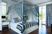 Four-poster bed with string curtains in black and white bedroom