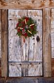 Winterlicher Türkranz an der Tür einer Holzhütte