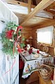 View of set table in wooden cabin seen through open wooden door with wreath