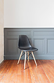 Black classic chair in front of dove grey wainscoting