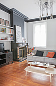 Coffee table sofa and fireplace in living room in shades of grey