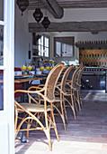 Blick von der Terrasse in Speisesaal mit gedeckten Frühstückstischen und Vintage Geflechtstühlen