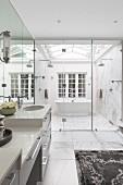 Luxurious bathroom with ridge skylight over free-standing bathtub