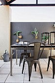 Metal-framed dining table and metal chairs on roofed terrace with foliage plants hung on grey wall