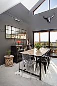 Langer Tisch im Industriestil und verschiedene Stühle in hohem Esszimmer mit anthrazitfarbenen Wänden