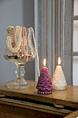 Two lit festive candles next to elegant pearl jewellery in glass jar