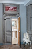 Verzierte Flügeltür und Blick in Bad mit nostalgischem Flair