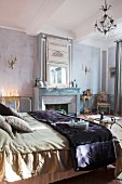 Double bed, mirror on chimney breast and arrangement of candles in sophisticated bedroom