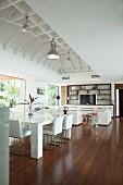 Offener Wohnbereich im Strandhaus mit weißen Designermöbeln