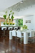 Elegant white dining area and opulent flower arrangements in beach house