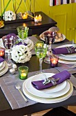 Table festively set with artificial flowers, tealights an elegant colourful wine glasses