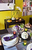 Table festively set with lot tealights in front of white artificial flowers on black console table