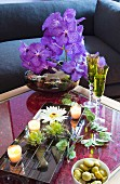 Arrangement of artificial flowers, bowl of water and tealights on coffee table