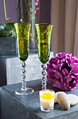 Elegant green Champagne flutes, purple artificial flower and lit tealight