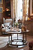 Antiquarischer, runder Tisch mit Teegeschirr, Kerzenständer und Panettone