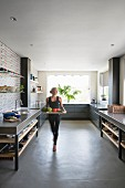 Woman carrying tray through large modern kitchen in shades of grey