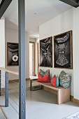 Pictures of African jewellery above colourful cushions on bench