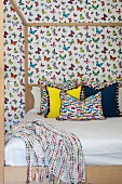 Colourful scatter cushions on modern four-poster bed against butterfly-patterned wallpaper