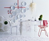 Decorative wall plates and red chair in white, futuristic dining room