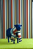 Blue sheep statue wearing scarf and sunglasses in front of striped wall