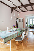 Colourful tablecloth on long table, classic chairs and pendant lamps with light bulbs in dining room