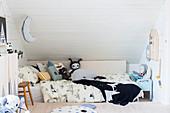 Kinderbett mit Stofftieren im Dachgeschoss-Kinderzimmer