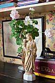 Religious figurine, potted geranium and books on desk