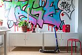 Two low metal lockers below graffito on wall
